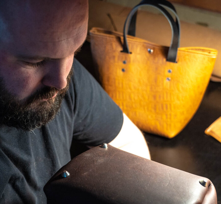 artisan working on handmade australian tote bag in chocolate brown tan cow leather